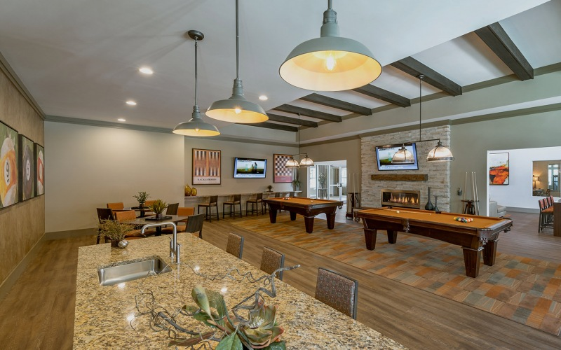 Large well lit game room with bar seating and two billiard tables