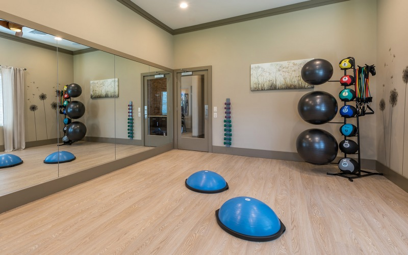 Large yoga room with a large window and weighted balls.