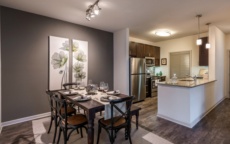 Spacious and well lit dining area with wood floors and access to the living room